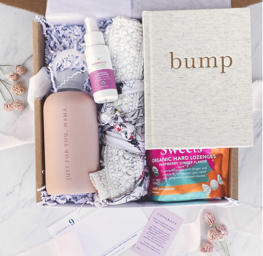 Nurtured 9 say congrats box with a water bottle, robe, baby journal and other small gifts inside a gift box