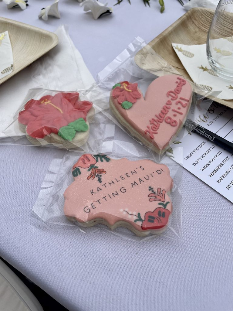 """personalized cookies that read """"Kathleen's getting Maui'd"""" with painted hibiscus and sparkles"""
