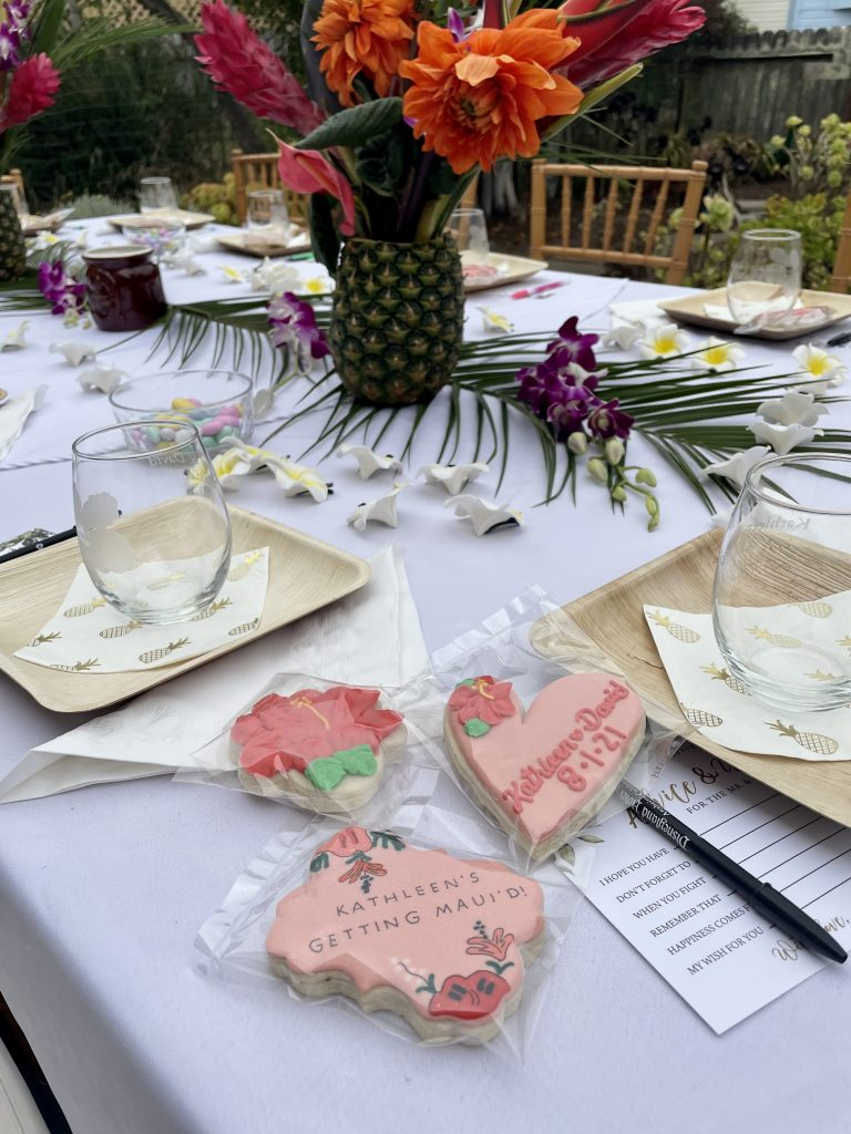 tropical wedding shower table decorations with pink tropical cookies, bamboo plates and cocktail napkins with pineapples on them