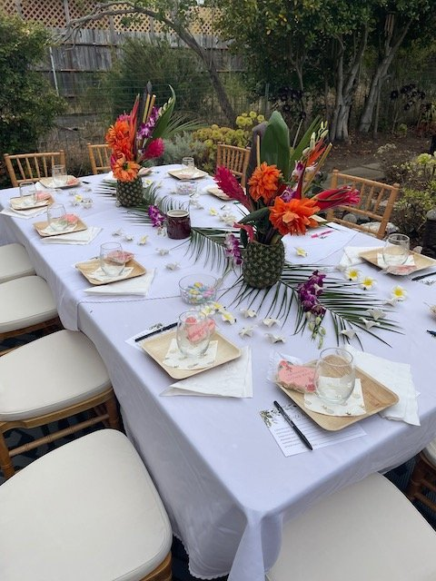 Decorated table for wedding shower with tropical flowers, bamboo plates and pink cookies