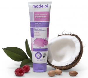 MadeOf natural sunscreen pink and purple bottle with coconut and raspberries around it.