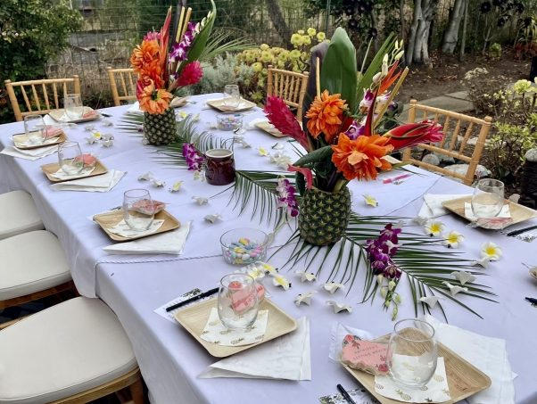 tropical bridal shower table set for 12 guests with pineapple centerpieces, fresh tropical orange and red flowers, bamboo plates and pink custom cookies