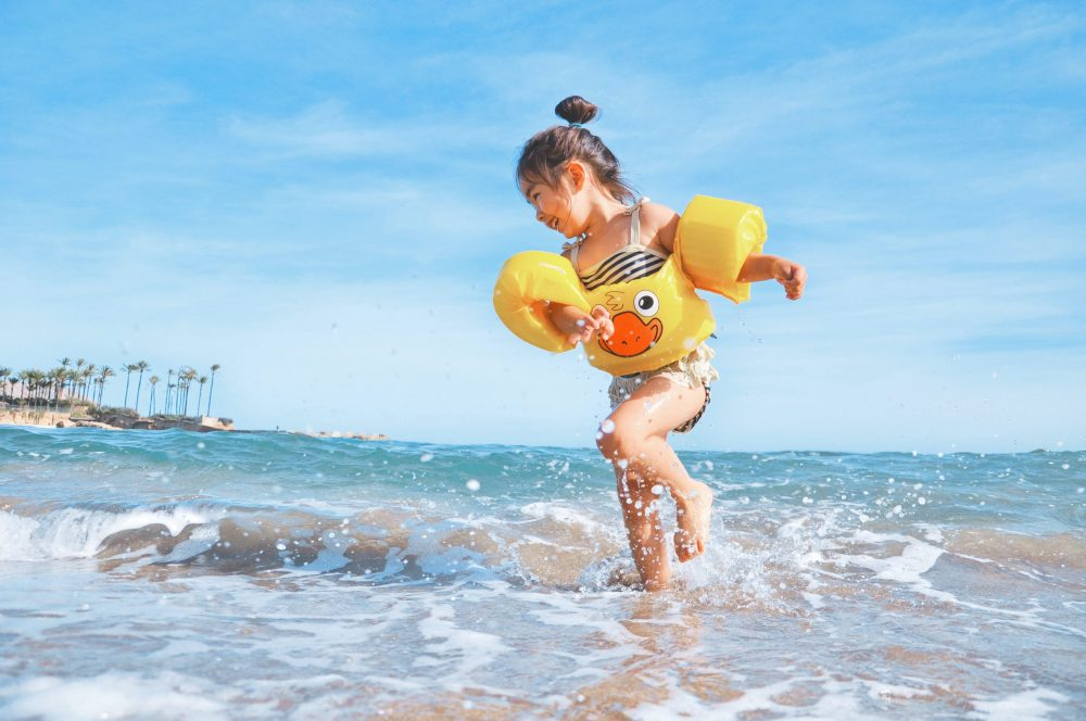 Young child playing in waves at the beach with a yellow ducky floaty on